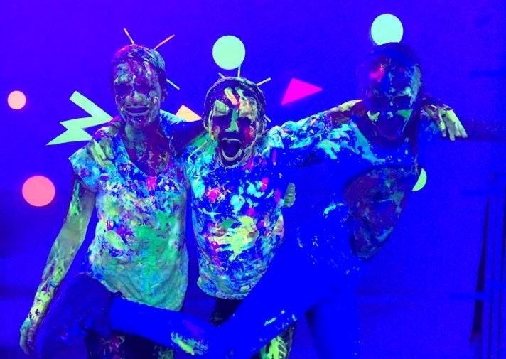 three kids in glow in the dark with neon paint on